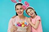 Happy holiday! Mother and her daughter with painting eggs. Family preparing for Easter. Cute little  poster