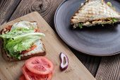 Sandwiches On Plates On A Wooden Surface. One Sandwich And Tomatoes With Onions On A Wooden Plate, T poster