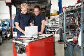 Mechanics working on laptop in auto repair shop
