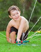 Young boy or kid cools off by playing in water sprinkler at home in his back yard on hot summer day