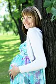 Portrait of young pregnant woman in summer park
