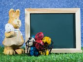 Many Colorful Of Easter Eggs Placed In Front Of Blackboard With Easter Rabbit. Blackboard With Color poster