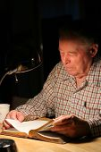 Elderly Man Reading His Bible Under Lamplight.