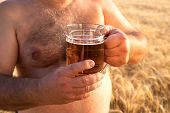 A Glass Of Beer Is Held By A Fat Man In The Background Of A Barley Field, A Glass Of Beer Standing O poster