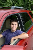 A newly licensed teenage male driver sits in his shiny new red car. Close up in vertical format show