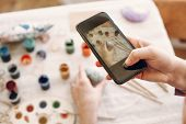 Hands Holding Phone And Taking Picture Of Easter Flat Lay With Colorful Eggs And Paint On Table. Hap poster