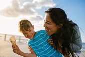 Boy Eating An Ice Cream Standing Near Seafront With His Mother. Little Boy Holding An Ice Cream Cone poster