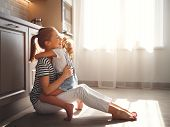 Family Mother And Child Daughter Hugging In Kitchen On Floor. poster