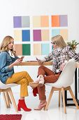 Magazine Editors Working With Smartphones At Workplace With Color Palette On Wall poster