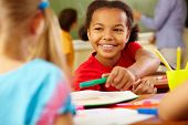 image of environment-friendly  - Portrait of cute girl giving crayon to classmate at lesson - JPG