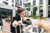 Pensive Business Woman At Cafe Veranda Using Personal Computer For Working Digital Social Media. Han poster
