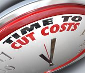 stock photo of slash  - Watch your spending and reduce your overhead by paying attention to this clock telling you it is Time to Cut Costs and get your budget in order before you are in debt or bankrupt - JPG