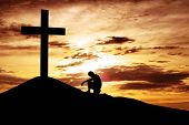stock photo of cross hill  - A man making a confession to the cross shot under dawn sky - JPG