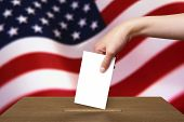 foto of ballot-paper  - Hand With Ballot And Wooden Box On Flag Of USA - JPG