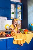 Little Girl Is Sitting On Kitchen Table With Jar Of Jam. Cheerful Child In Kitchen. Little Cook. Kit poster