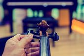 Hand Tuning Violin With Blurry Piano In Music Room Or Stage. poster