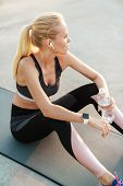 Image of concentrated sportswoman in tracksuit drinking water during workout on fitness mat outdoors poster