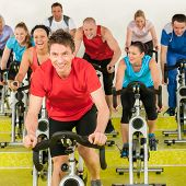 Fitness instructor leading spinning class people exercise enjoy physical workout