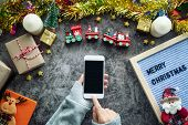 Online Shopping For Christmas Season And Gift Festival. Hand Holding Mobile Phone With Blank Screen  poster