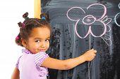 Little mulatto girl draws on the board