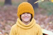 Keeping Head Warm In Fall. Happy Child Wear Knitted Hat On Autumn Day. Small Kid Enjoy Fall Style. L poster