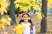 Autumn Melody. Happy Little Girl Wear Headphones On Autumn Landscape. Cute Child Listen To Music In  poster