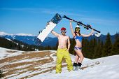 Happy Young Couple In Goggles, Sexy Woman In Bikini And Snowboarder Man With Bare Torso Holding Skis poster