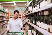 Jovem olhando para garrafa de vinho no supermercado