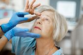 Doctor Or Nurse In Medical Gloves Dripping Eye Drops On Eyes Of A Senior Patient During A Treatment  poster