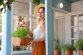 Young Woman With Basket Of Home Plants On Veranda poster