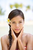 Spa woman wellness beauty woman portrait. Natural outdoors portrait of multicultural woman showing natural beauty looking at camera with flower in the hair. Mixed race Asian Caucasian girl in tropics.