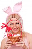 Blonde with bunny ears holding woven punnet with colorful Easter eggs, isolated on white