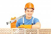 Male construction worker holding a bubble level and resting on a brick wall isolated on white backgr