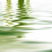 stock photo of greenery  - Reflection of greenery mirrored on the surface of calm rippled water for a background of tranquillity and wellbeing - JPG