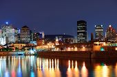 stock photo of highrises  - Montreal over river at dusk with city lights and urban buildings - JPG
