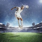 football player in white shirt striking the ball with head at the stadium under the rain
