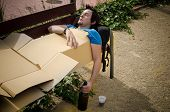 stock photo of hangover  - Guy sleeping off a tough hangover on a park bench - JPG