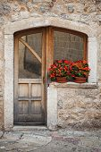Old Wooden Door With Red Flowers On The Windowsill