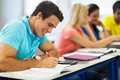 cheerful male uni student studying in lecture room