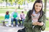 Portrait of a college girl text messaging with blurred students sitting in the park
