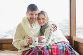 Portrait of a loving young couple in winter clothing with coffee cups against cabin window