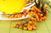 picture of sea-buckthorn  - Branches of sea buckthorn with tea on bamboo mat close up - JPG