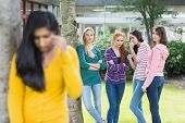 stock photo of peer-pressure  - Female student being bullied by other group of students - JPG
