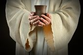 The hands of Jesus holding wine cup, symbol of communion