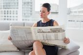 Beautiful young businesswoman reading newspaper on sofa at a bright home