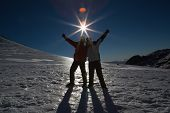 Full length of a silhouette couple standing with hands raised on snow covered landscape against the