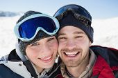 Close-up portrait of a cheerful couple with ski goggles on snow covered landscape