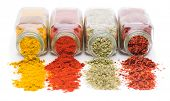 image of mixture  - Assortment of spices spilling from glass spice jars - JPG