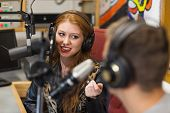 stock photo of redheaded  - Attractive happy radio host interviewing a guest in studio at college - JPG