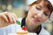 Happy head chef putting mint leaf on little cake in professional kitchen